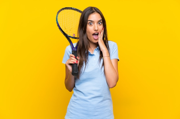 Young tennis player woman with surprise and shocked facial expression