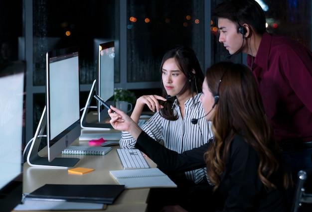 젊은 태국 아시아 고객 서비스 관리 운영자는 야간에 직장에서 고객 지원을 돕기 위해 콜 센터에서 야간 근무를합니다.