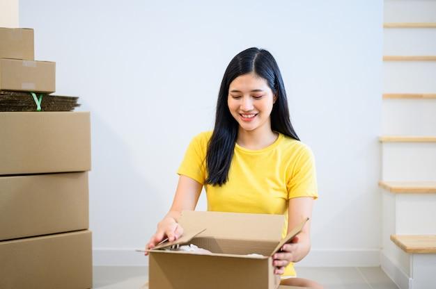 箱を詰める若いタイの女性起業家。オンラインショッピングと宅配。封鎖して自宅で仕事をします。 covid後の新しい正常と生活。
