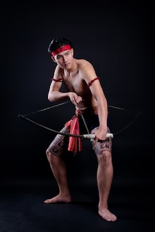 Young thailand male warrior posing in a fighting stance with a bow on black