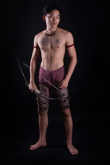 Young thailand male warrior posing in a fighting stance with a bow
