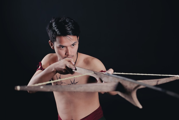 Young thailand male warrior posing in a fighting stance with a sword