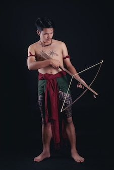 Молодой таиландский воин позирует в боевой позе с мечом