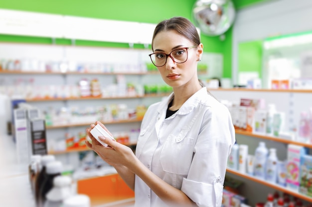 A young thin brown - haired lady with glasses, dressed in a white coat, looks at the camera and holds a small jar in the lobby of a new pharmacy. .