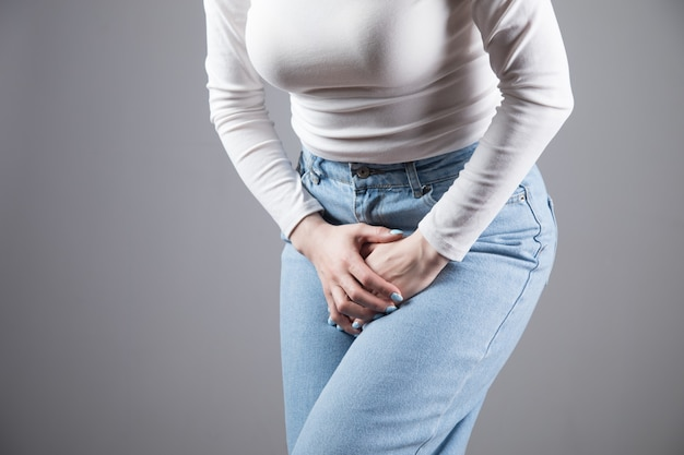 A young thin girl in jeans keeps her hands sandwiched between her legs. women's health, gynecology on a gray scene