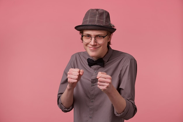 A young thin guy elegantly dressed with a hat glasses in a shirt and bow tie puts forward his fists as if going to fight threatens someone isolated on a pink background.