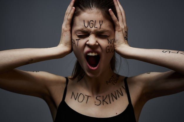 Young thin woman with insults on the body inscriptions, bad words, depressed state, loneliness