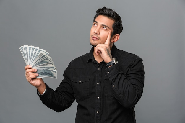 Young thinking concentrated man holding money.
