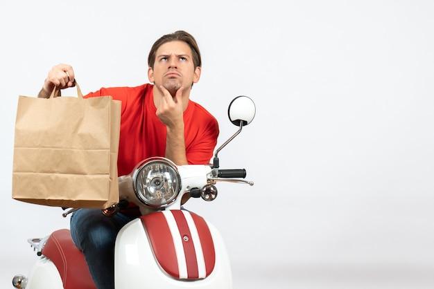 Молодой думающий курьер в красной форме сидит на скутере и держит бумажный пакет на желтой стене