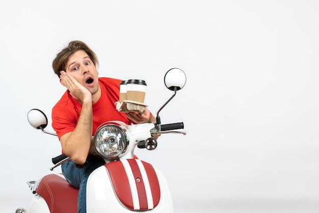 Молодой думающий курьер в красной форме сидит на скутере и держит заказы на желтой стене