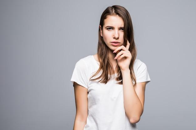 白いtシャツとジーパンの若い思考の女性は白いスタジオの背景の前に滞在します。