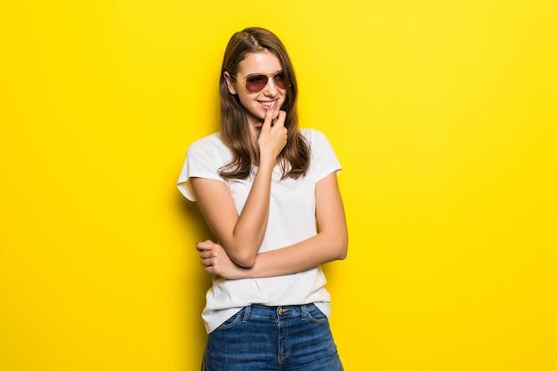 白いtシャツとジーパンの若い思考の女性は黄色のスタジオの背景の前に滞在します。