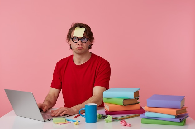 Young thinking man in glasses wears in red t-shirt, with a sticker on his forehead, sits by the table and working with notebook and books, looks up and suppose, isolated over pink background.