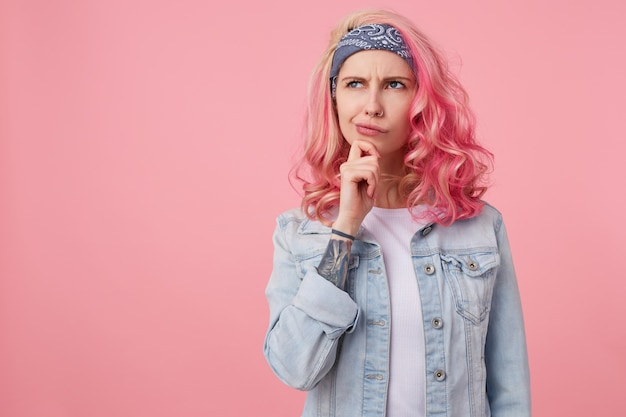 Young thinking nice woman with pink hair, stands copy space, looks up thoughtfully and touches the cheek with his finger, wears a white t-shirt and denim jacket.