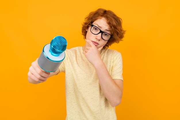 Young thinking red-haired guy in a shirt and glasses on a yellow background