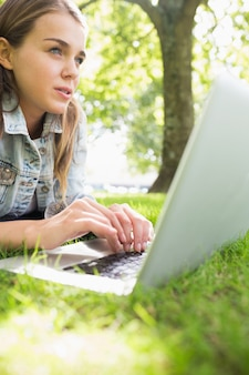 Young thinking student lying on the grass using her laptop