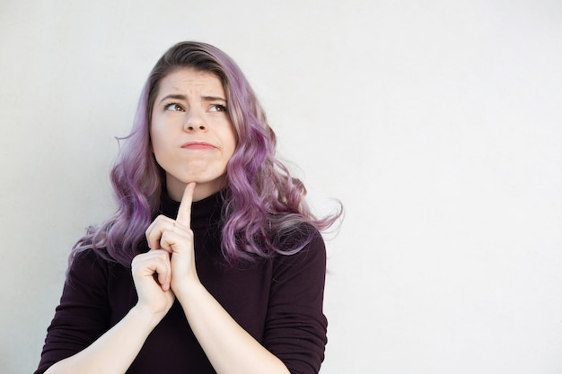 Young thinking woman with purple hair posing over a grey background. empty space