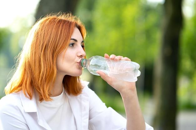 夏の公園でボトルから水を飲む若い喉が渇いた赤毛の女性