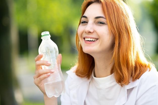 Молодая жаждущая рыжая женщина пьет воду из бутылки в летнем парке