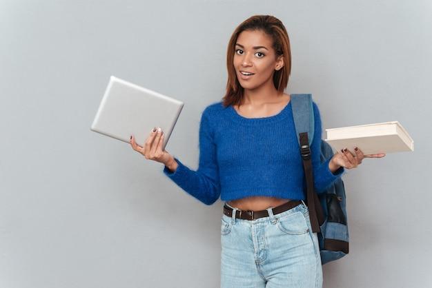 タブレットコンピューターと本のどちらかを選択するバックパックとセーターとジーンズの若い思慮深いアフリカの女性