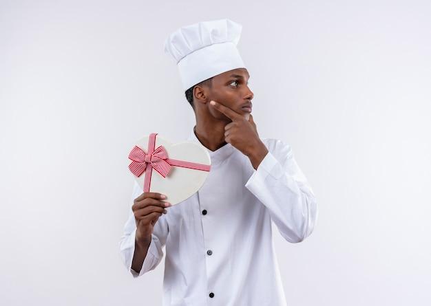 Il giovane cuoco afroamericano premuroso in uniforme dello chef tiene la scatola a forma di cuore e mette la mano sul mento isolato sulla parete bianca
