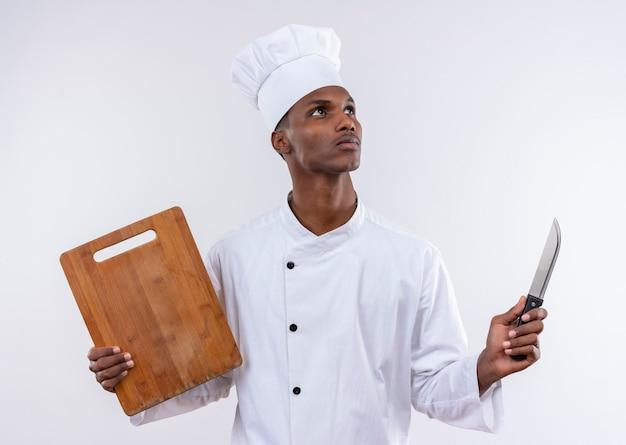 Il giovane cuoco afroamericano premuroso in uniforme del cuoco unico tiene lo scrittorio e il coltello di cucina di legno isolati sulla parete bianca
