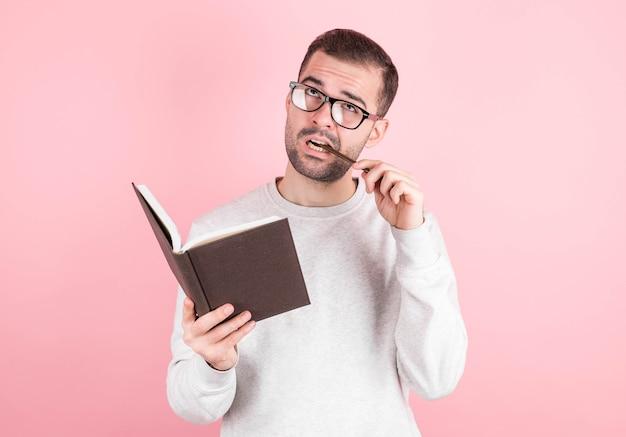 テストについて考えている眼鏡の若い思慮深いひげを生やした男