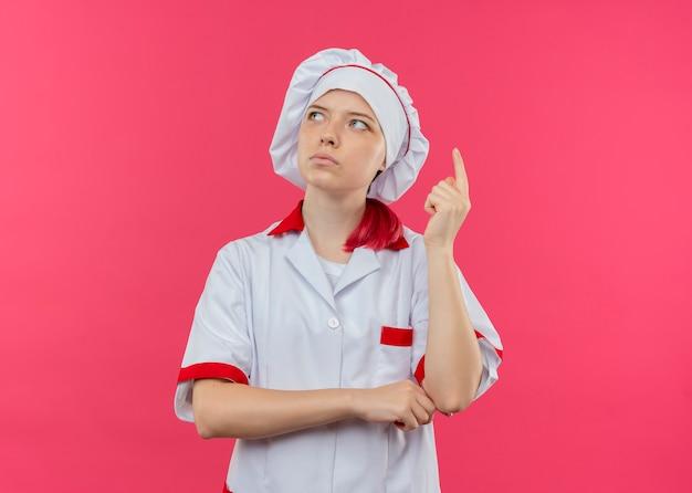 シェフの制服を着た若い思いやりのある金髪の女性シェフが上を向いて、ピンクの壁に隔離された側に見えます