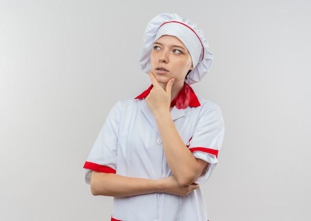 シェフの制服を着た若い思いやりのある金髪の女性シェフは、白い壁で隔離のあごに手を置きます