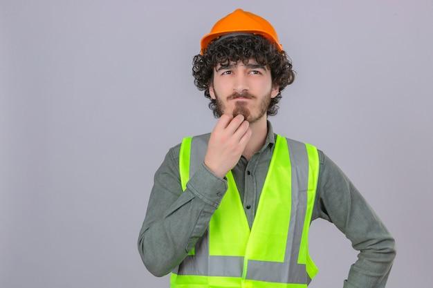 孤立した白い背景の上にあごを考えて困惑した表情で立っている若い思慮深いパン粉ハンサムエンジニアワーカー