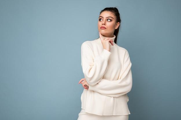 腕を組んで、あごに手を上げてカメラを自信を持って見える青い背景の上に分離された白いカジュアルセーターを着ている若い思慮深いブルネットの女性。前向きに考える。