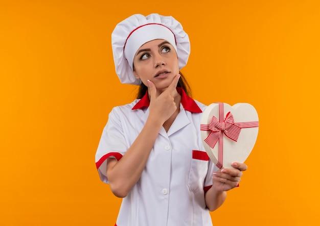 La giovane ragazza caucasica premurosa del cuoco in uniforme del cuoco unico tiene la scatola di forma del cuore e mette la mano sul mento isolata sulla parete arancione con lo spazio della copia