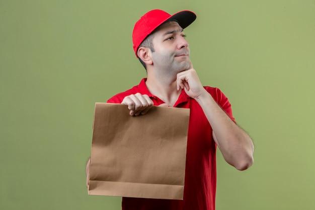 고립 된 녹색 배경 위에 의아해 턱에 손으로 제쳐두고 찾고 종이 패키지를 들고 빨간색 유니폼을 입고 젊은 사려 깊은 배달 남자