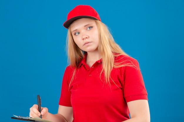 Giovane donna di consegna premurosa che indossa la maglietta di polo rossa e cappuccio che tiene un blocco per appunti con la penna che osserva da parte sopra fondo blu isolato
