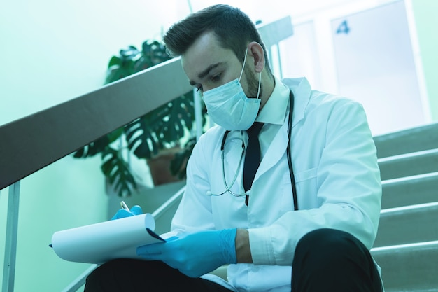 Young thoughtful doctor making last notes in the report after long shift