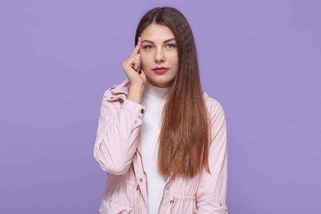 若い思慮深い女性は真剣な物思いに沈んだ表情をしており、寺院の近くに指を置き、淡いピンクのジャケットを着て、薄紫色の背景に立ち、カメラを見ます。