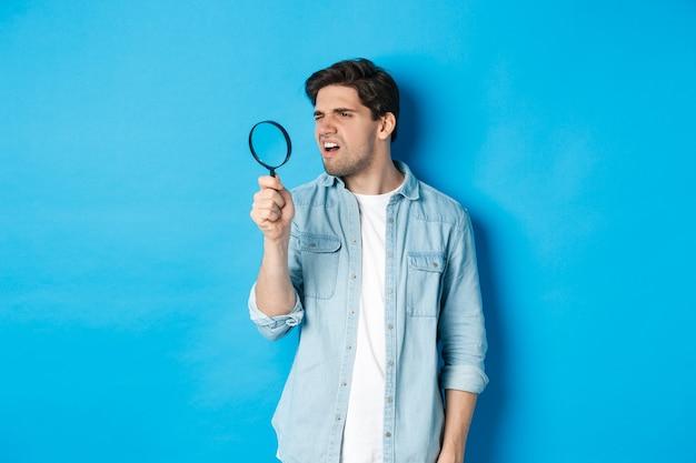 虫眼鏡を通して見て、小さな何かを読んで、青い壁の上に立っている若い思慮深い男