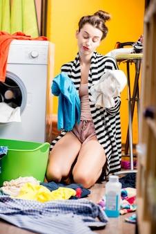 Молодая задумчивая домохозяйка сидит на полу в разноцветной одежде возле стиральной машины дома