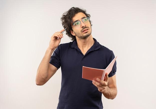 Il giovane uomo premuroso in camicia nera con vetri ottici tiene il taccuino e mette la penna sulla testa isolata sulla parete bianca