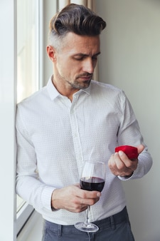 Young thoughtful man holding glass with wine and looking at box with ring