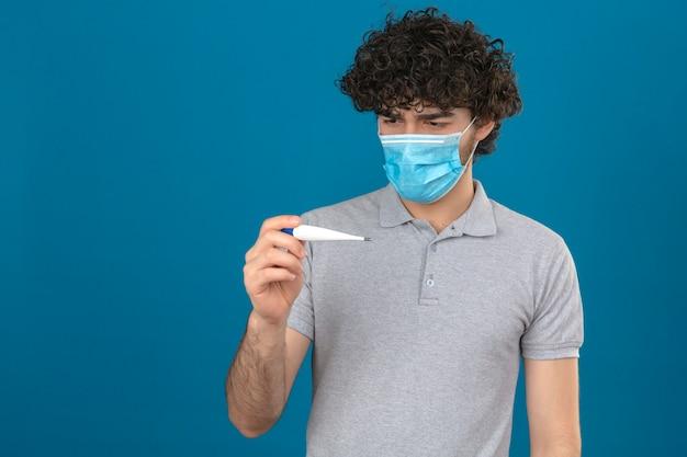 Молодой вдумчивый человек в медицинской защитной маске, глядя на цифровой термометр в руке в панике на изолированном синем фоне