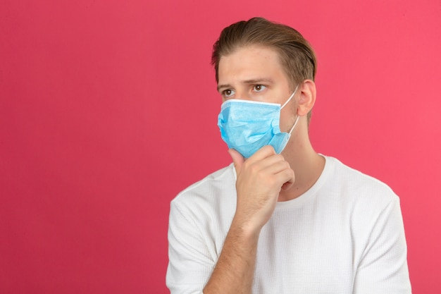 Giovane uomo premuroso in maschera protettiva medica toccando il mento e pensando su sfondo rosa isolato