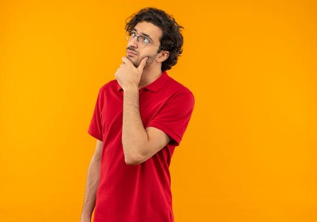 Giovane uomo premuroso in camicia rossa con vetri ottici mette la mano sul mento isolato sulla parete arancione
