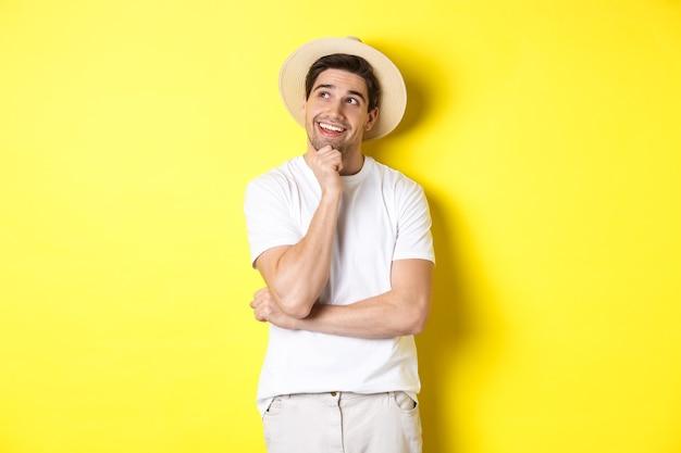 何かをイメージし、左上隅を見て、笑顔、考え、黄色の背景の上に立っている若い思慮深い男の観光客