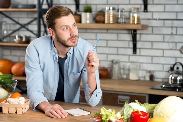 Young thoughtful man writing recipe in kitchen with pen and diary