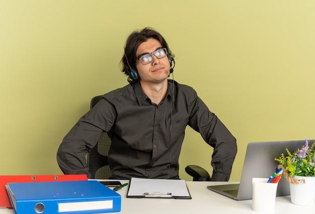 Uomo giovane lavoratore di ufficio premuroso sulle cuffie in vetri ottici si siede alla scrivania con strumenti per ufficio utilizzando il computer portatile e guarda a lato