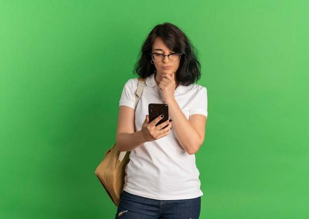 Young thoughtful pretty caucasian schoolgirl wearing glasses and back bag puts hand on chin looking at phone on green  with copy space
