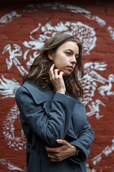 Молодая задумчивая красивая девушка в сером пальто и водолазке позирует перед стеной из красного кирпича с граффити