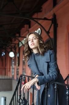 赤い建物の前で灰色のコートとタートルネックのポーズで若い思いやりのあるかわいい女の子。魅力的な女性のストリートスタイルのポートレート写真撮影、美しいエレガントなモデルの都会的な写真撮影
