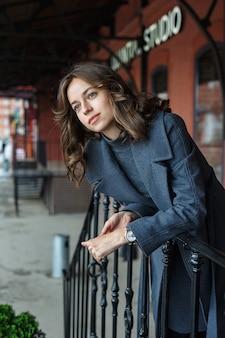 Молодая задумчивая красивая девушка в сером пальто и водолазке позирует перед красным зданием